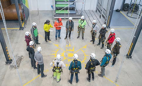 Workers in a Safety360 circle with manager checking PPE
